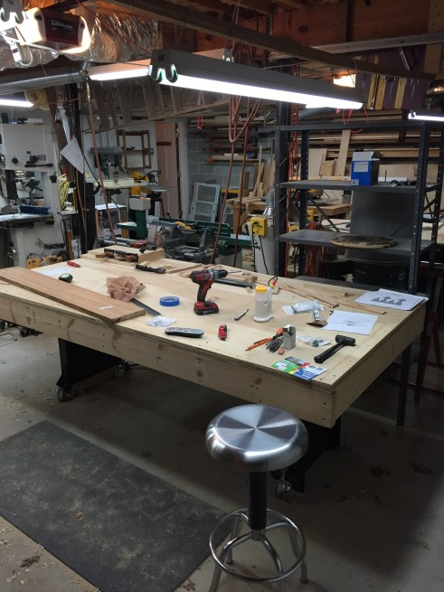 "This is my almost ultimate assembly table. Why? Because it is BIG, 4' x 8' with plenty of room for everything you need, and within arms reach. It's built from 2 sheets of 3/4"" ply screwed to a 2x6 frame, and it is nearly dead flat. What you can't see is the other reason it's so special. It sits on a Noden Adjust-A-Bench leg set that adjusts height wise from below my waist to chest height (I'm 5'11""). It's the better part of $500 and is built from heavy guage steel, but is worth every penny. I built my own stretchers and caster set. It's remarkably solid too. I would not trade this thing for the world!"