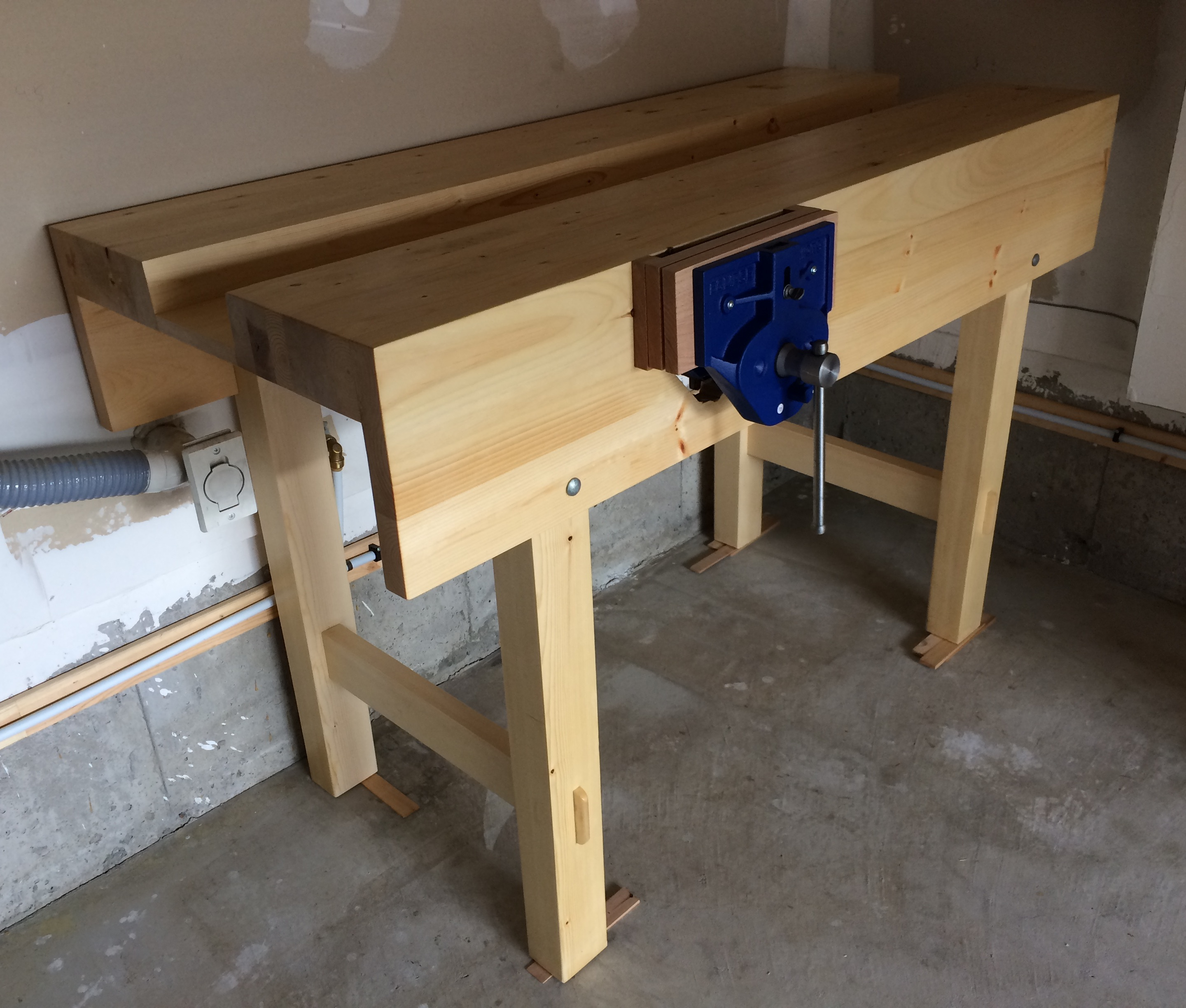 "Workbench: made from dimensional SPF, 65cm x 150cm, 97cm high. Finish: two coats of shellac, wax. Eclipse 9"" QR vise with red oak pads. — This was my first big project. It took me two months of weekends to make. Hand planing round corners of knotty two-by-fours was painful but valuable experience. I had to sharpen my plane every half an hour. Squaring the aprons was time consuming: I had to rebuilt them three times because they kept twisting overnight. I can safely say I learned a lot while building this bench by using hand tools only. Despite all mistakes and imperfections, I'm happy now. — When you make your project, remember: Never give up."