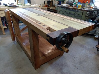 """Just finished my workbench. Not Paul's design, but used several of his techniques in building it. At 69 years old I have learned so much from watching his videos and am teaching my 15 year old grandson all I can. All joints are mortise and tenon using Oak dowels to draw pin them together. Wood was all material I have accumulated over the past 40 years, Poplar, Cherry, Black Walnut, Oak and Spruce. Thought Paul would appreciate some of the """"upcycling"""" I did on the vises, using old horse drawn machinery parts."""