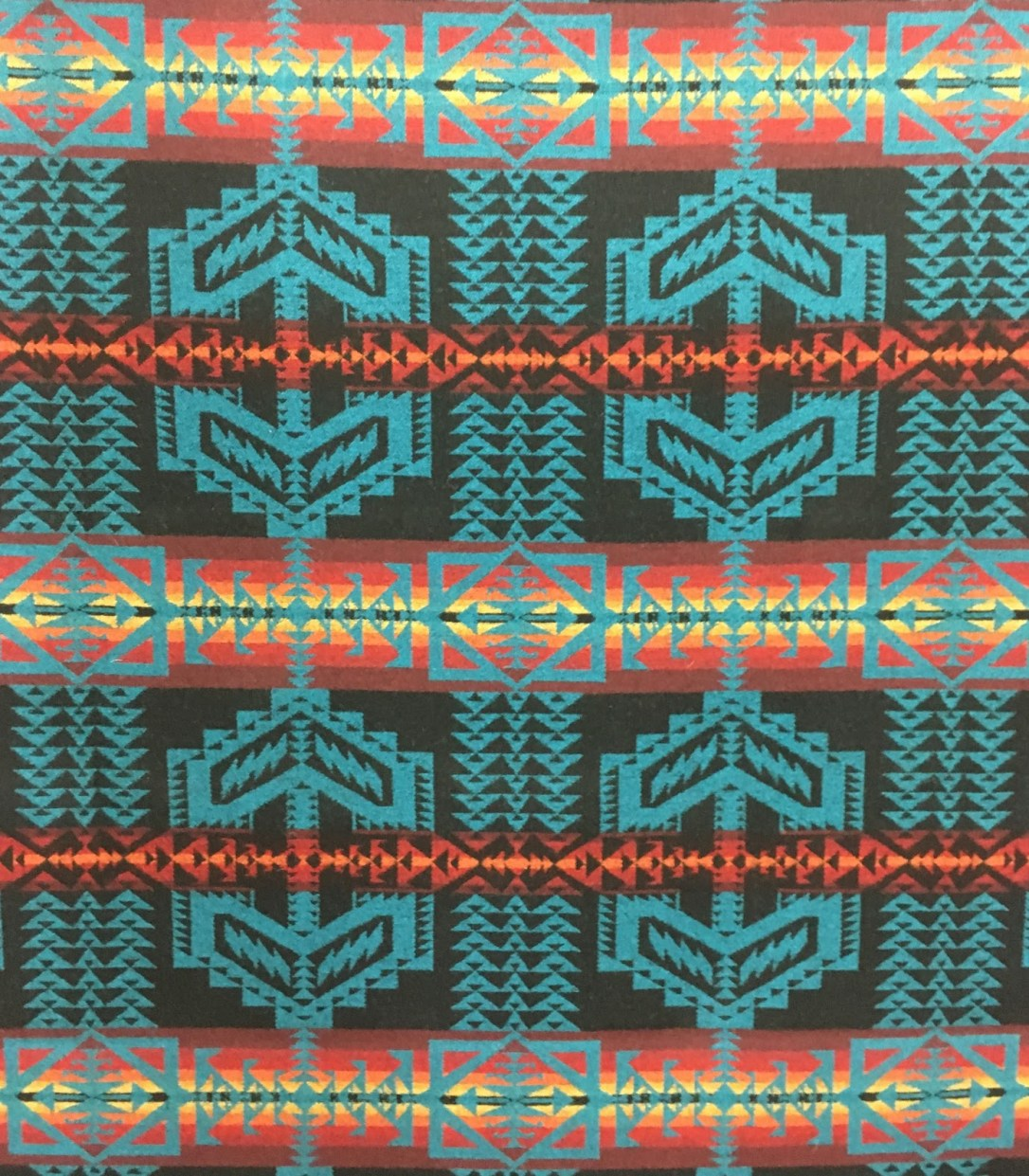 Swatch of Pendleton wool fabric in Turquoise Trail, with black background and bold geometric pattern in bright colors, with turquoise medallions and stripes of red, orange and yellow.