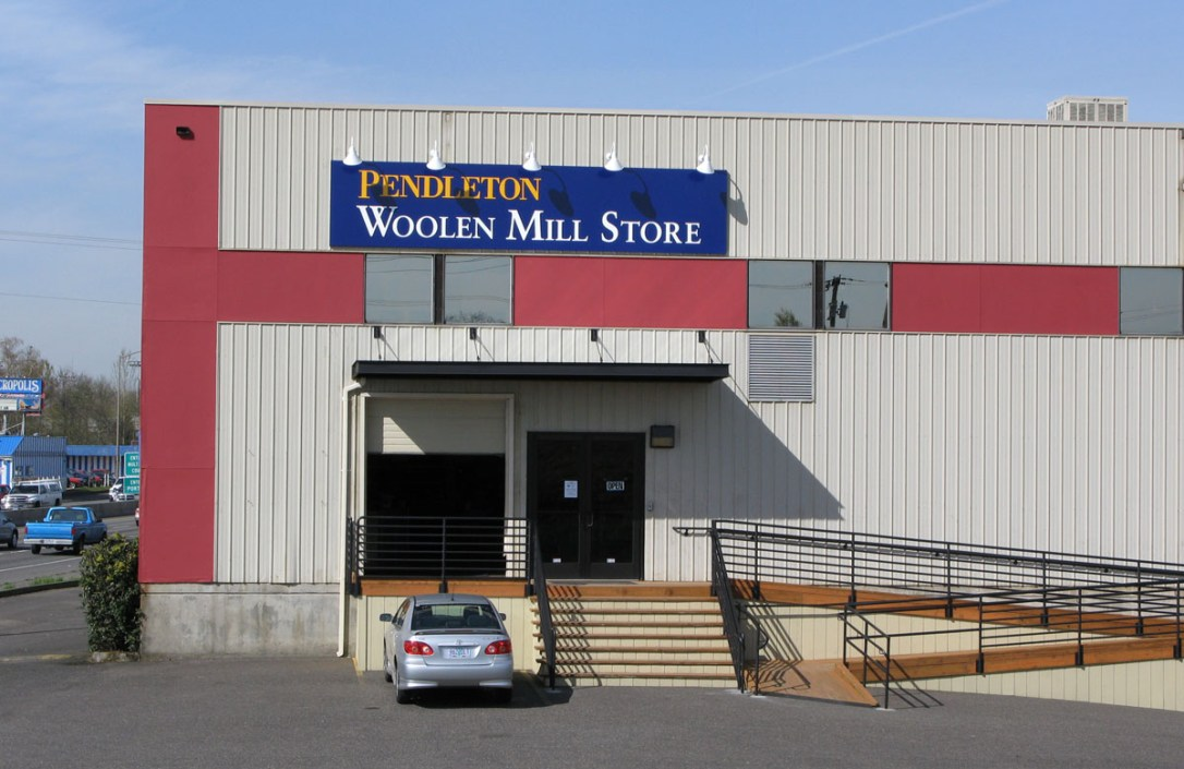 Photo of the entrance of the Woolen Mill Store entrance on a sunny day; stairs and ramp, pull up garage door, double glass doors, silver car parked in parking lot.