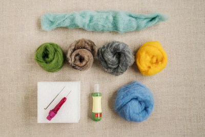 Pendleton Color Play wool roving; six pieces of wool roving arranged on a grey background, with a square of white styrofoam and a sharp needle tool for wool felting.