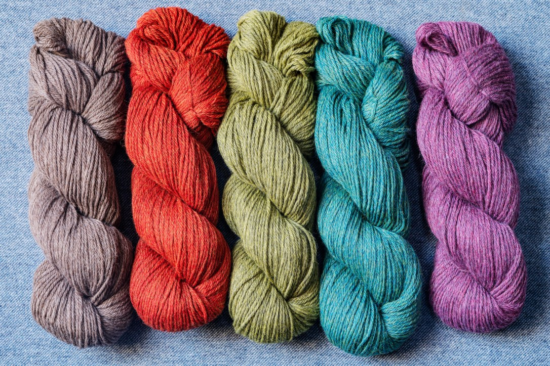Pendleton yarn, five skeins, arranged on a blue denim background. Wool colors are grey, rust, green, teal and purple.