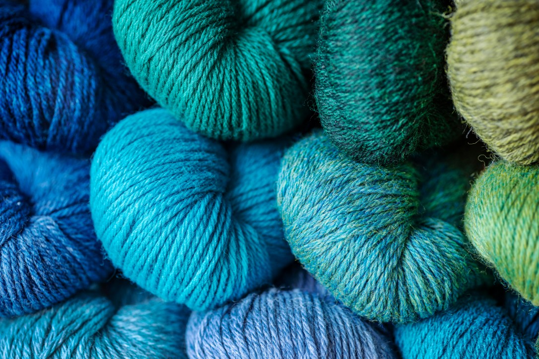 The ends of eleven skeins of wool yarn in shades of blue, green and purple.