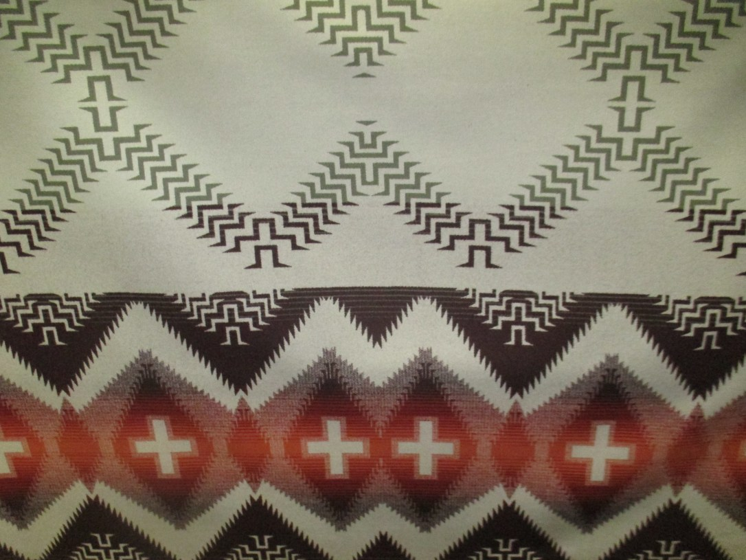 Swatch of Pendleton fabric in Beargrass Mountain, a cream background with a pattern of brown and rust that mimics basket weaving.