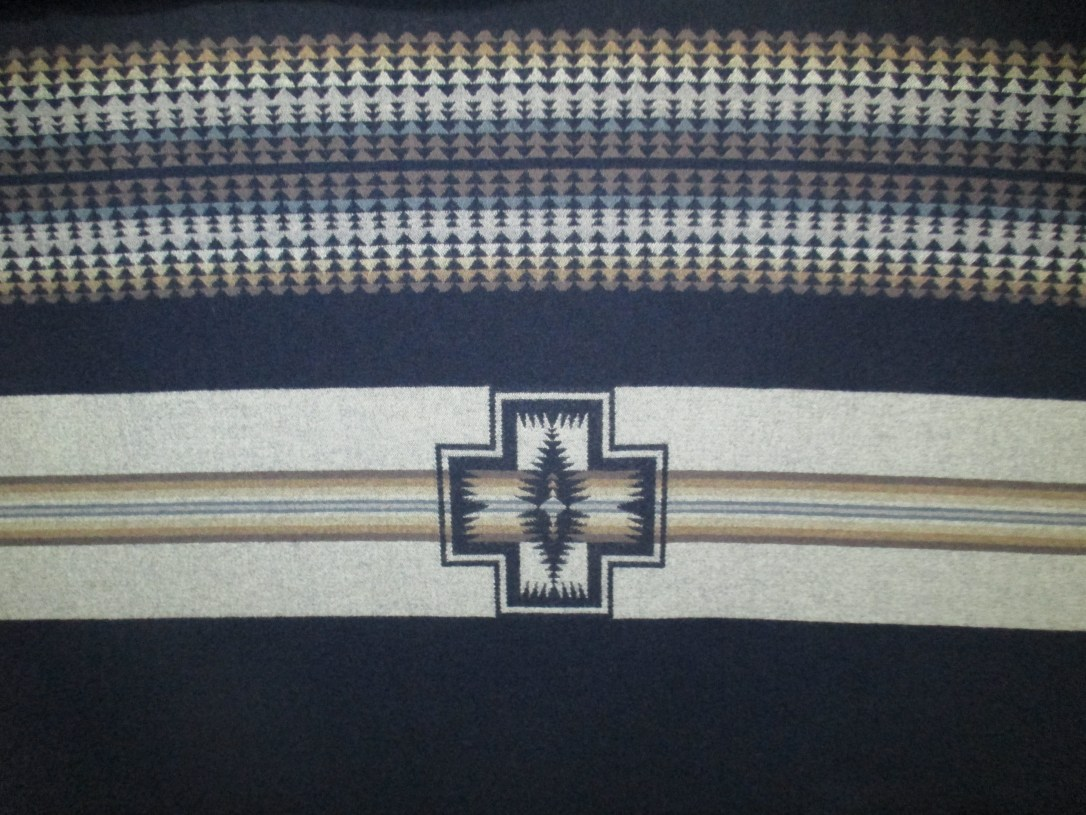 Swatch of Pendleton wool fabric in a border print with mostly navy blue background, with stripes of ivory, tan and light blue covered with small navy blue arrows, and an intermittent Harding medallion on a stripe of ivory.