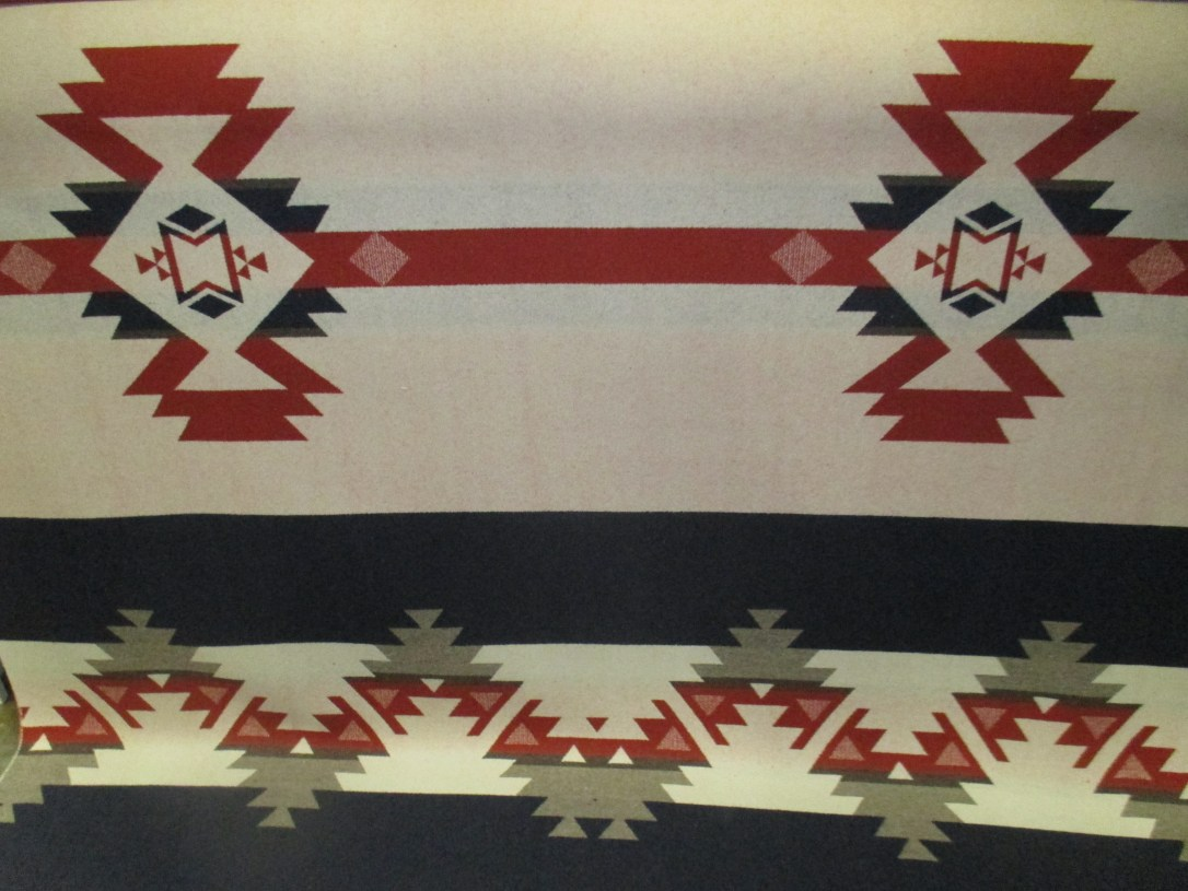 Swatch of Pendleton wool fabric in tan, grey and red with an ivory background.