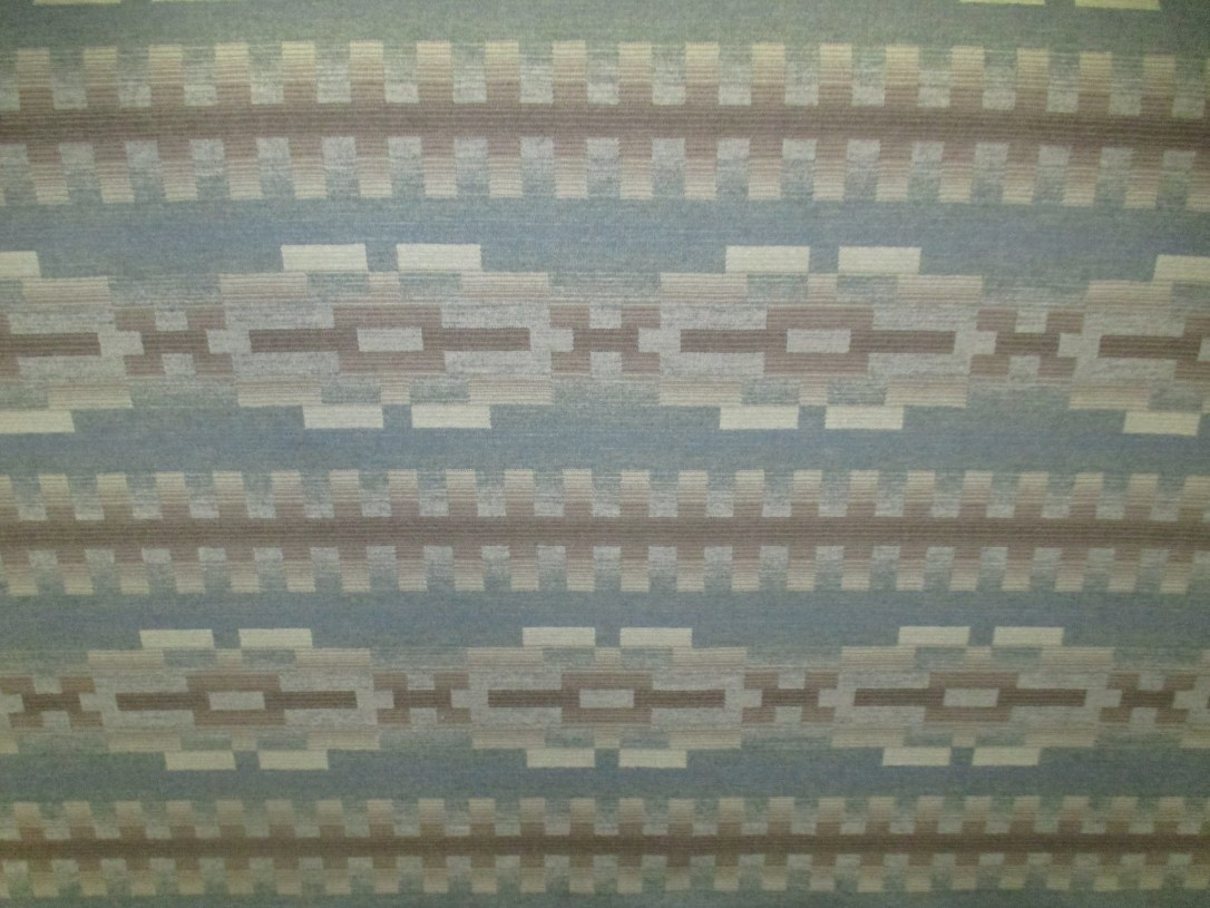 A swatch of Pendleton fabric in Pino Trail, a geometric pattern with lines of light blue, light brown, and ivory.