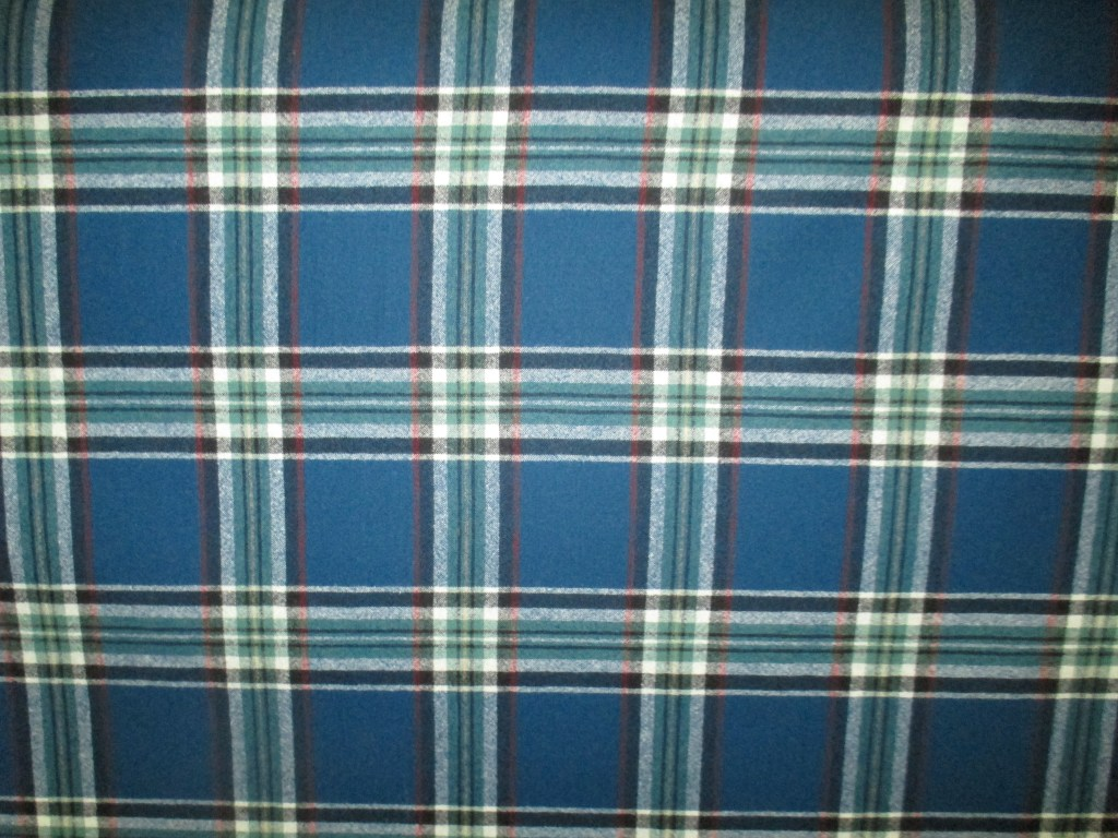 Swatch of pendleton fabric with a black and white plaid on a deep turquoise background.