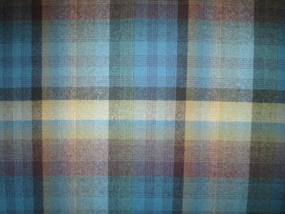 Swatch of Pendleton wool fabric in a plaid of charcoal, gold, and plum on a turquoise background.