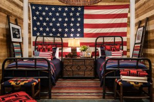 A room with wood plank walls, one of which is covered with a huge American flang, against which sits two twin beds made up with pendleton wool blankets and pillows.