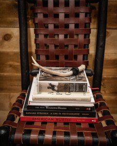 A wooden chair with seat and back made of woven strips of leather holds a stack of books and one antler.