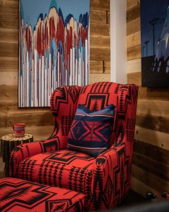 A chair and footstool uphosltered in red and black Pendleton wool fabric, against a wooden plank wall.