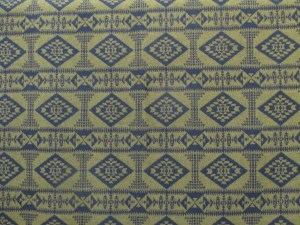 Swatch of Pendleton wool fabric in Basket Maker in Navy blue and deep bronzey-gold, a pattern of diamonds and columns in navy blue on the gold background.