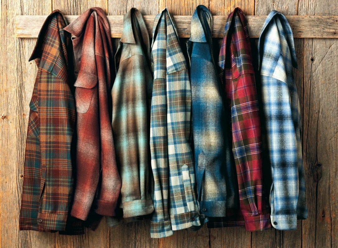 Seven plaid wool Pendleton shirts hanging on pegs in front of a wooden wall.