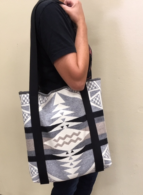 A woman stands with the jacquard tote bag slung over her shoulder.