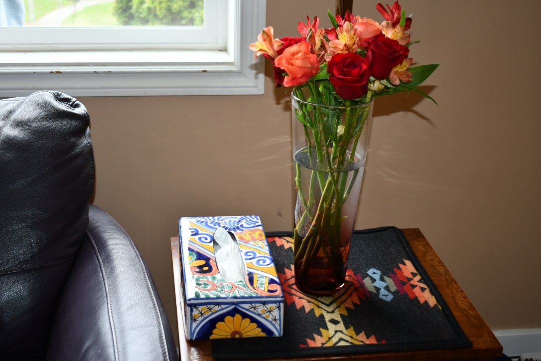 A woode end table sits next to a leather chair, with a piece of Pendleton Pueblo Dwelling wool fabric on top of the table, with a vase of bright flowers and a Kleenex box.