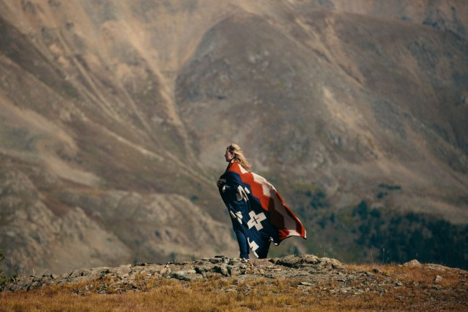 A woman wrapped in a Pendleton Brave Star blanket stands i a mountain canyon.