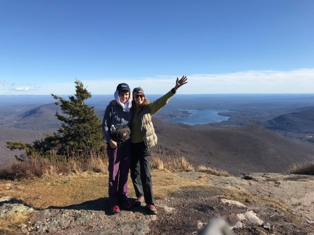 Two women stand on the top of a mountain.