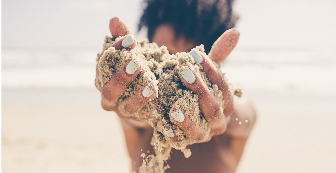 girl holding sand in front of her face