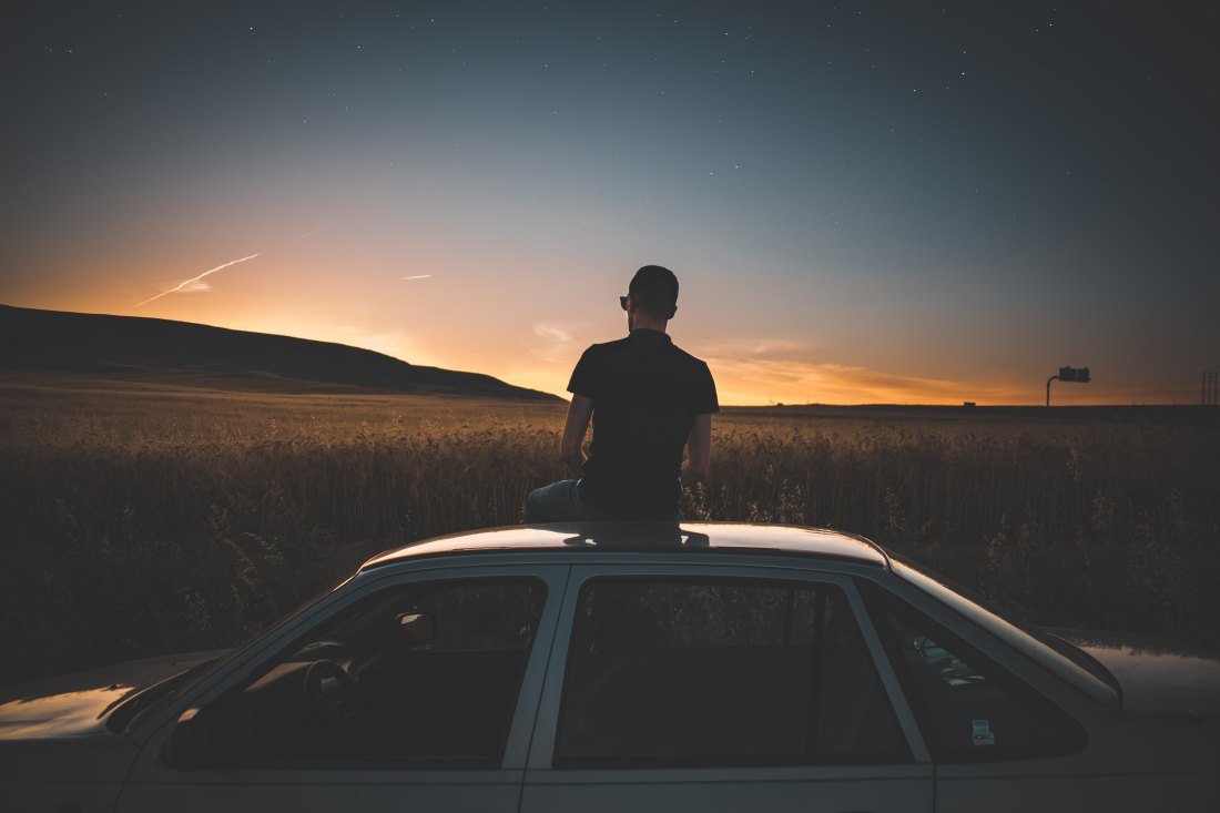man sitting on car in sunset