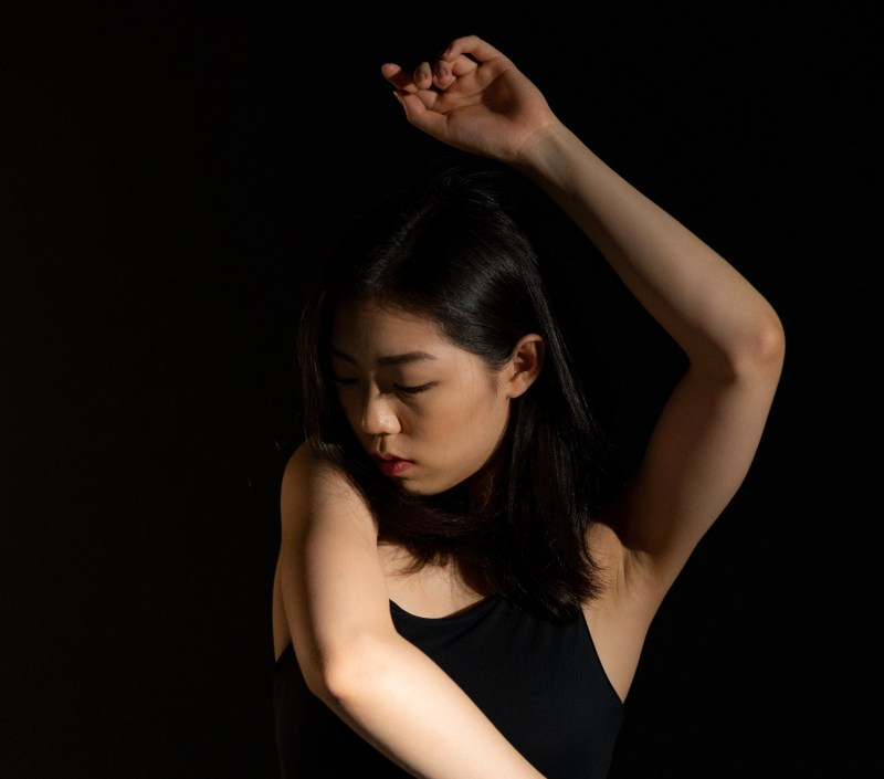 sensitive woman with her arms above her head looking down