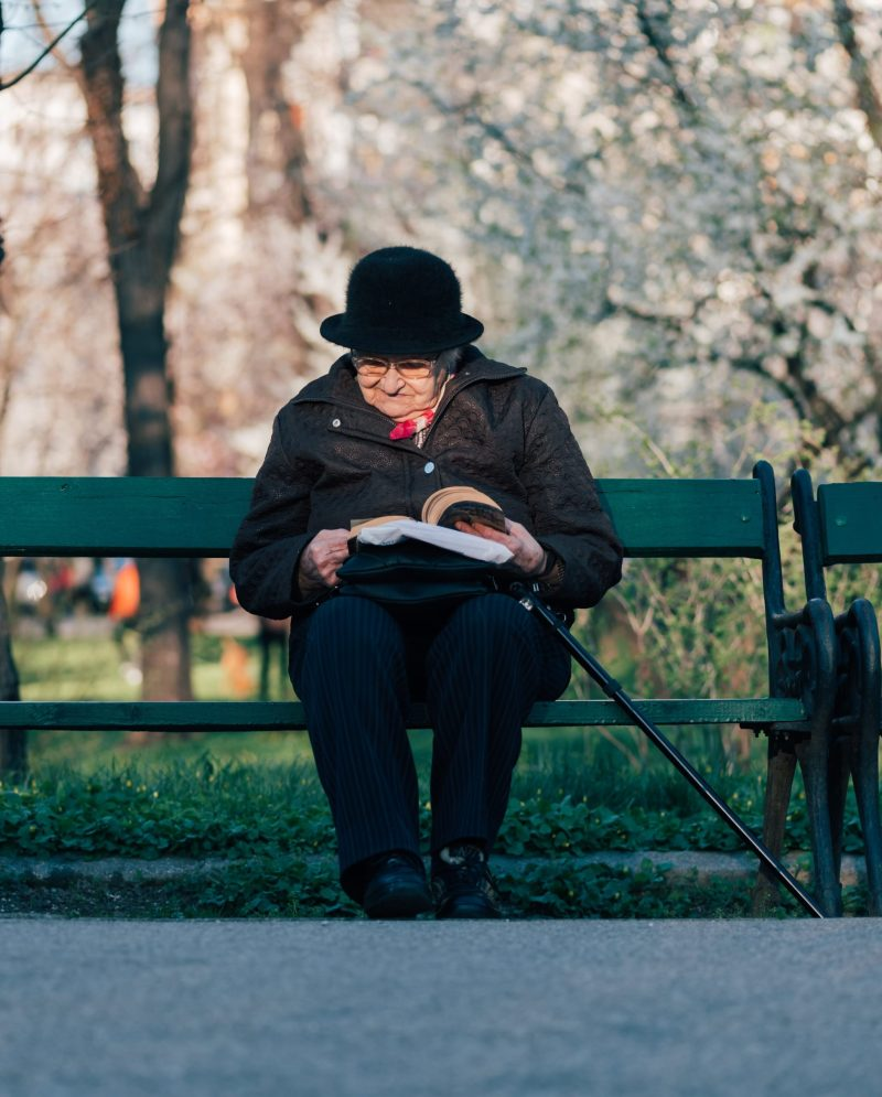 An older woman reading a book on a park bench