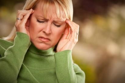 grimacing woman suffering a headache