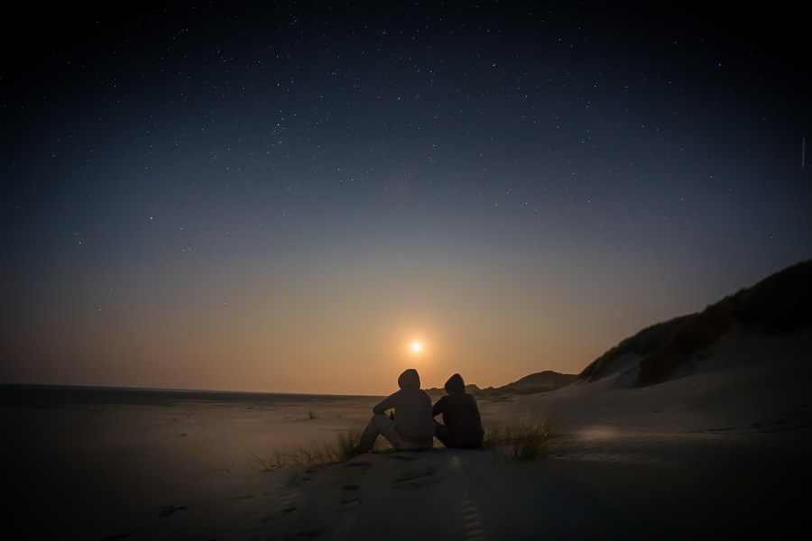 2 people sitting on a beach watching the sun disappear in the night sky