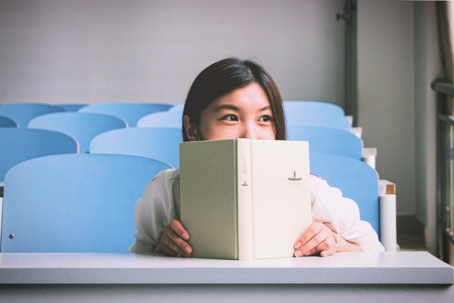 Girl in a classroom looking up from a book