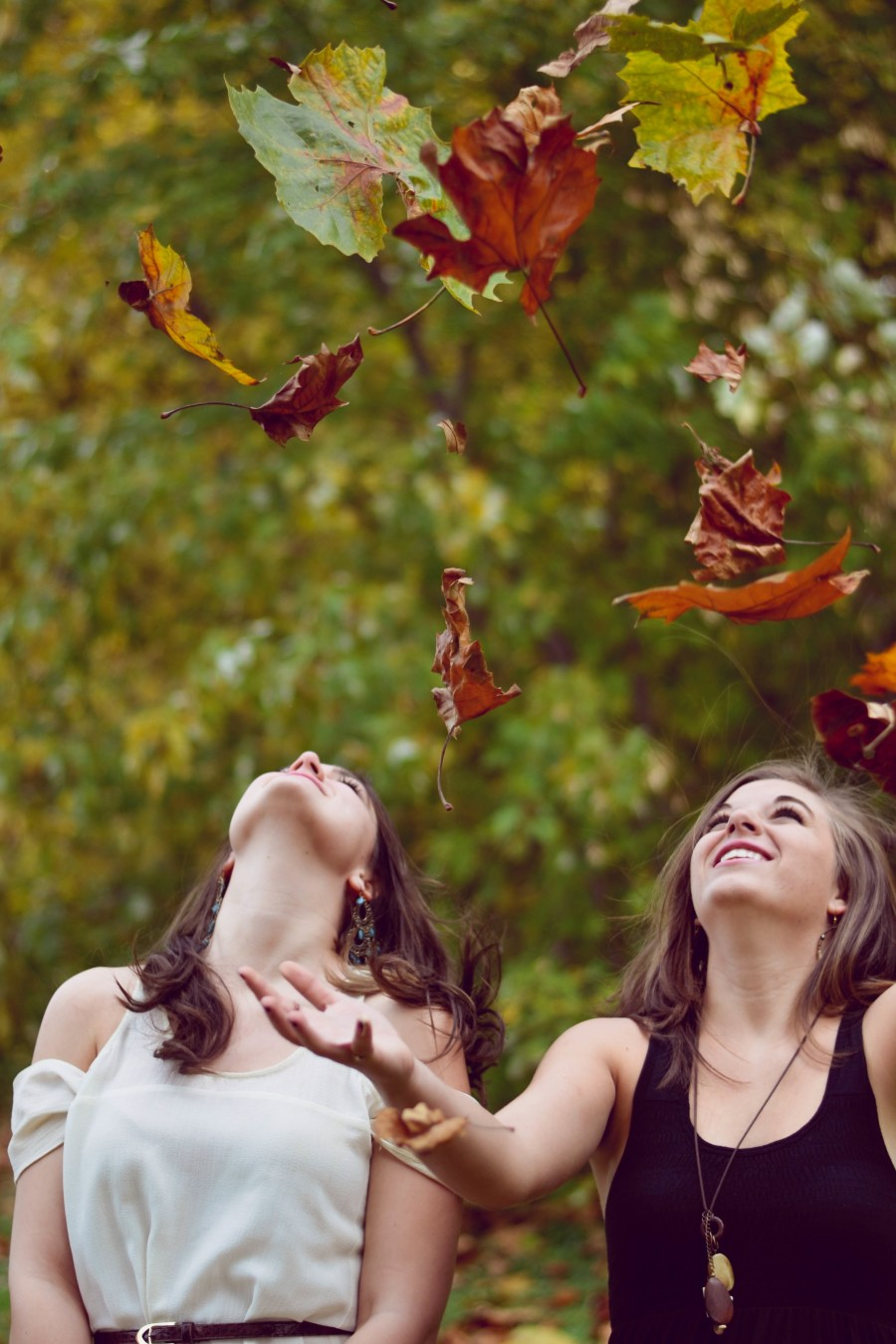 Two young women throwing autumn leaves in the air