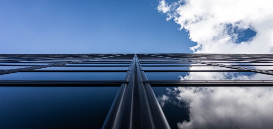 Looking up the side of a sky scraper to a blue sky with cloud