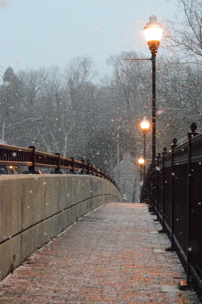 Foot bridge with snow falling