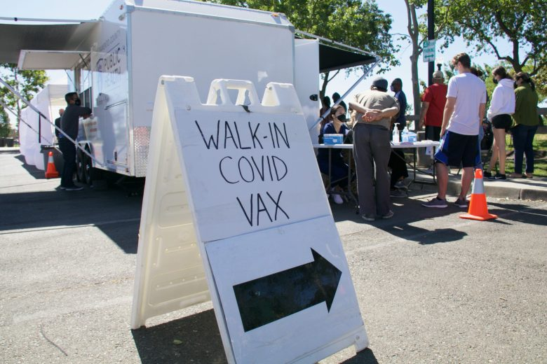 Walk-In COVID vax sign with arrow pointing to mobile vaccination stations