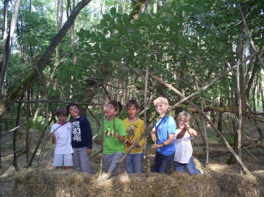 enfants devant la structure d'une hutte