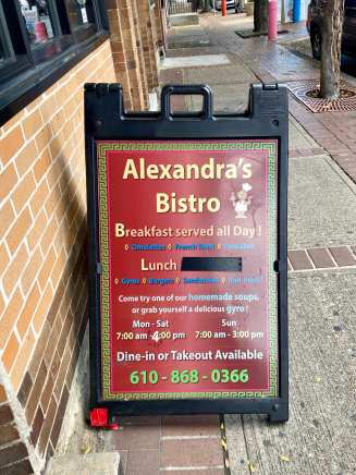 A pedestrian panel advertisement sits in front of Alexandra's Bistro on Saturday, Sept. 26, 2020, in Bethlehem, PA. The hours listed on the sign are not accurate as the restaurant has been closing around 2pm during the pandemic. (J24/Fern)