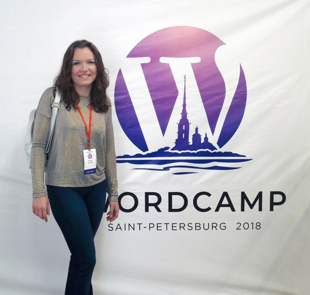 Olga next to a banner of WordCamp St Petersburg 2018