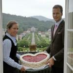 Eine Hochzeitstorte in Herzform ist nur einer der vielen Wünsche, die das Dorint Resort & Spa Bad Brückenau seinen Gästen erfüllt. Gastgeber Julia und Constantin von Deines präsentieren die süße Leckerei auf dem Balkon des Logenzimmers mit Blick in den Schlosspark.