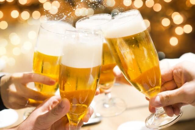 泡が満タンの生ビールのグラスを重ねて乾杯