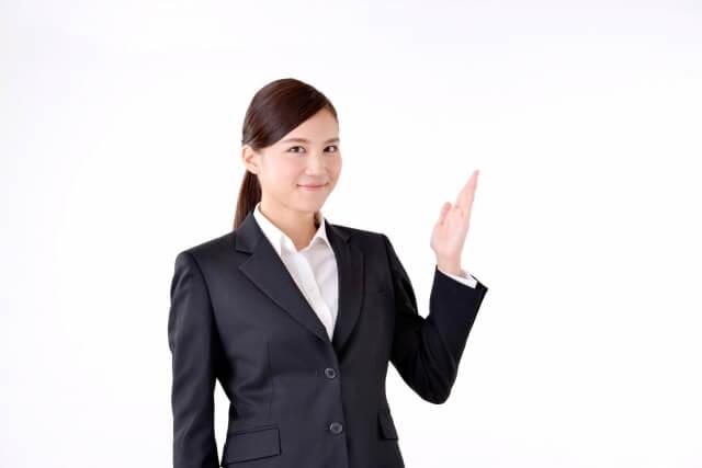 左手を上げ,案内するスーツ姿の女性