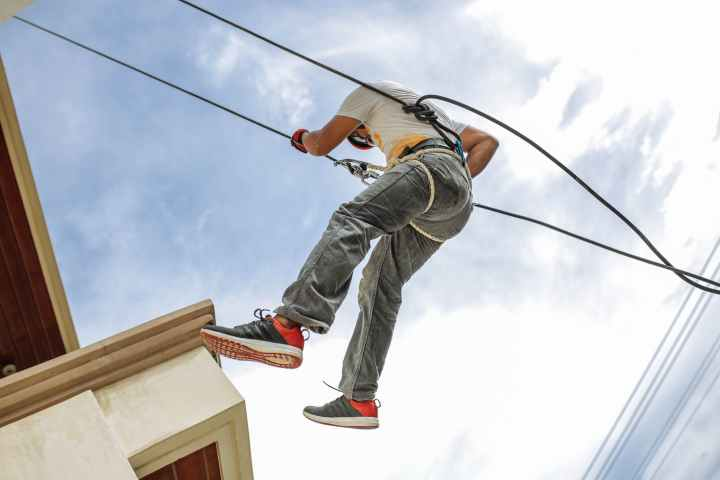 man wearing harness going down building