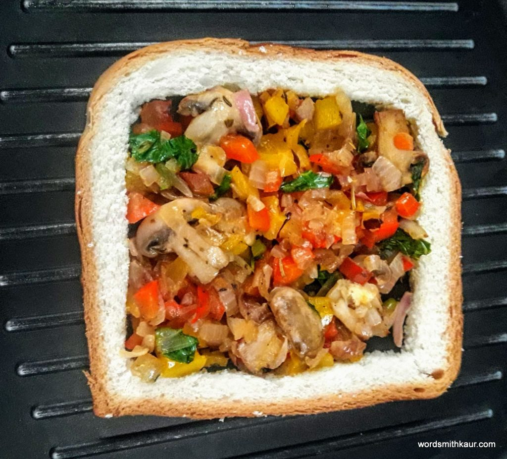 The base of this Egg in a Hole Recipe, is a bread slice and onion, peppers, mushroom and kale tossed in butter and herbs and enriched with cheese.