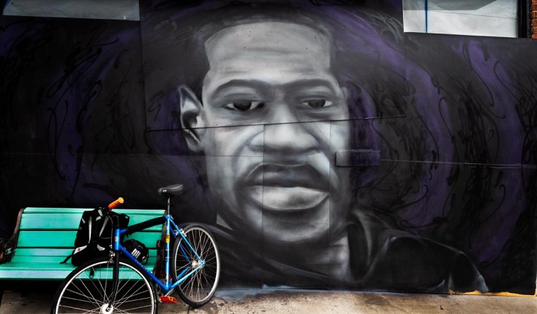 Blue bicycle leaning against aqua bench in front of painting of George Floyd with swirling black and purple background.