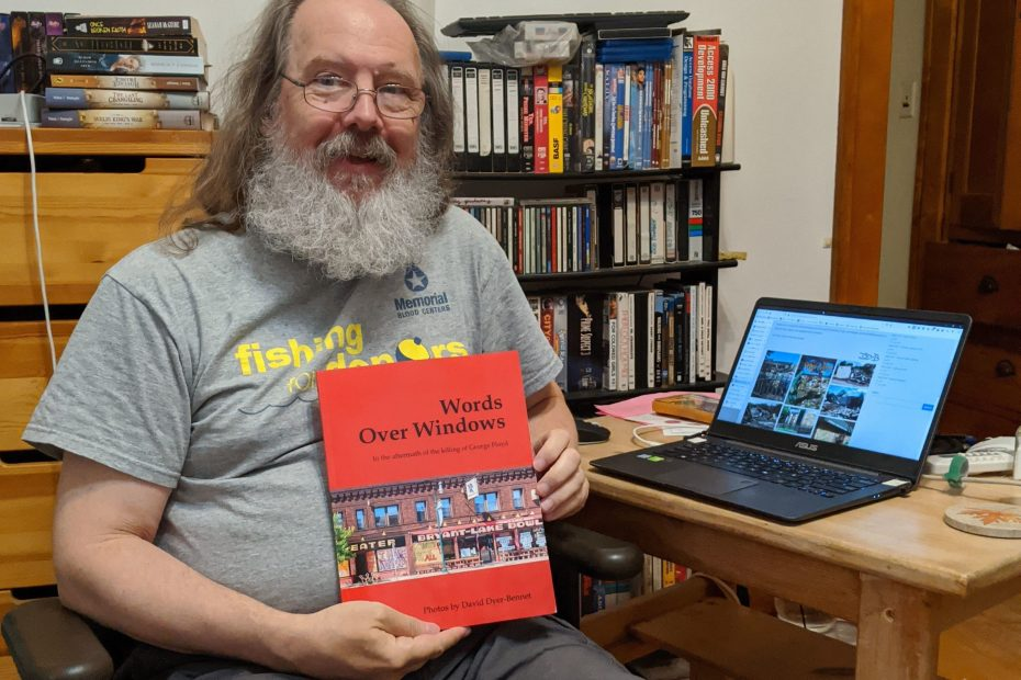 Me at my laptop, holding one of the author's copies of the book