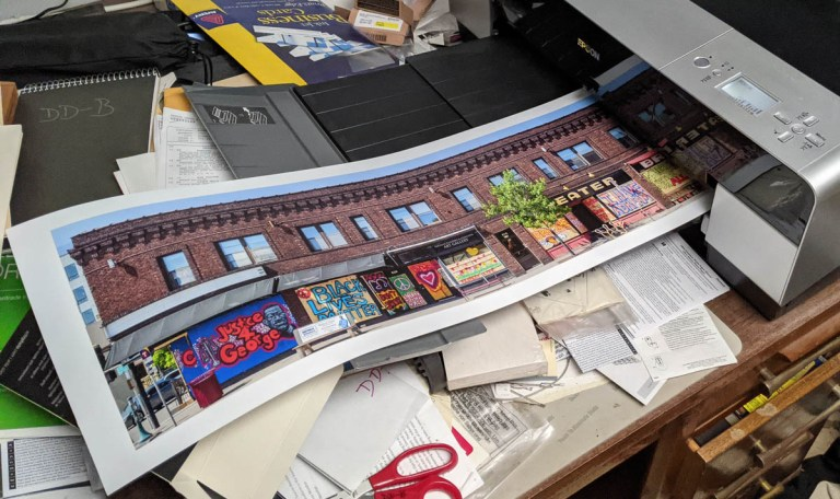 Book cover image, mostly out of the printer, overflowing the receiving tray