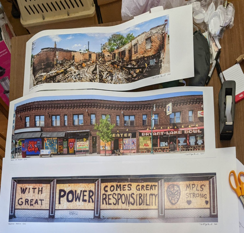 Three panoramic prints on a very messy table