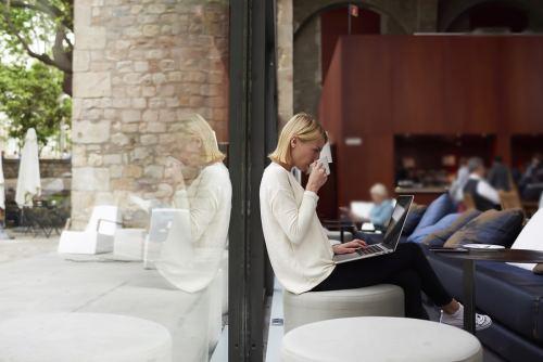 Female freelancer at distance work via net-book and drink tea