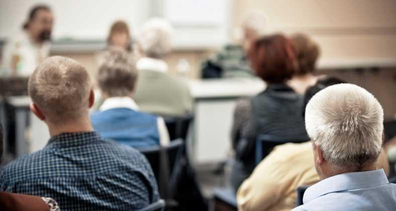 Un groupe d'hommes et de femmes assistant à un séminaire. | A group of men and women attending a seminar.