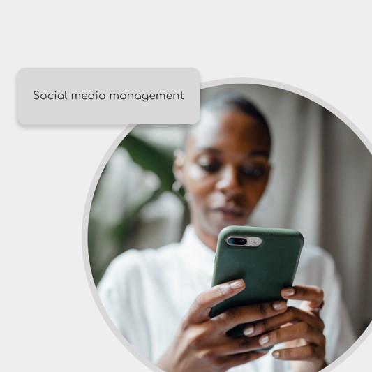 A blurred image of a dark skinned woman with a shaved head look at a mobile phone, with the words socil media management over the top