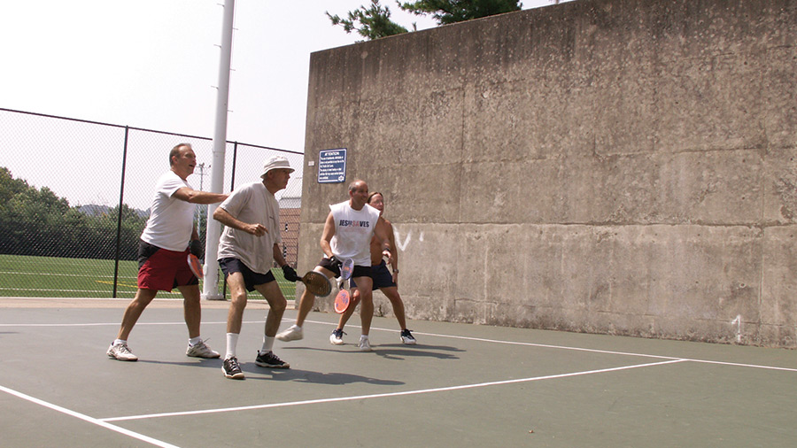 4 men playing paddleballin an outdoor court